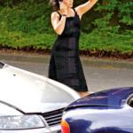 Frau mit Handy nach einem Auffahrunfall